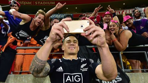 TOPSHOT - New Zealand's Sonny Bill Williams takes a selfie with fans during the cup final against South Africa on the second day of the Wellington Sevens rugby Union tournament at Westpac Stadium in Wellington on January 31, 2016. AFP PHOTO / MARTY MELVILLE / AFP / Marty Melville        (Photo credit should read MARTY MELVILLE/AFP/Getty Images)