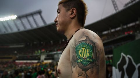 An Ultra supporter of Beijing Guoan shows a tattoo of the team's badge during a match against Chongcing Lifan.