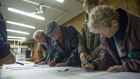 People sign in as they arrive at a Democratic Party caucus in Keokuk, Iowa.