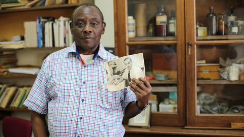 """Entomologist Louis Mukwaya holds a picture of Alexander Haddow, the scientist who first identified Zika virus in 1947. """"He was a very hardworking man,"""" Mukwaya said of Haddow. Mukwaya has been working at the institute since 1965."""