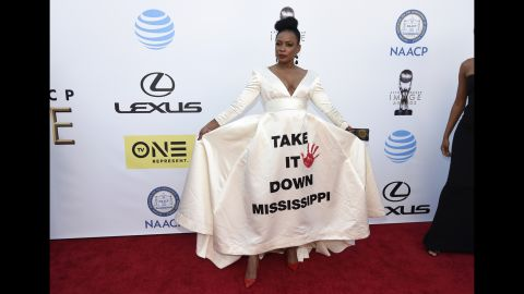 """Aunjanue Ellis arrives at the 47th NAACP Image Awards on Friday, February 5. The """"Quantico"""" star wore a white dress emblazoned with the phrase """"Take It Down Mississippi,"""" a reference to ongoing debate over the state flag, the last in the country to incorporate the Confederate battle emblem."""