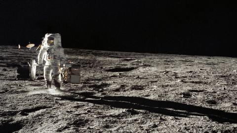 Bean carries equipment on the moon during the Apollo 12 mission.