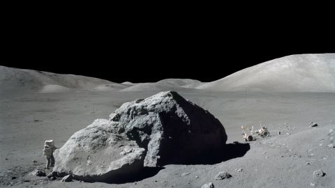 Schmitt stands next to a huge lunar boulder during an Apollo 17 moonwalk. The lunar rover is in the background. Schmitt was the 12th man to set foot on the moon, but Cernan was the last to leave.