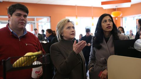 Democratic presidential candidate former Secretary of State Hillary Clinton (C) prepares to order food at a Dunkin Donuts with New Hampshire state campaign director Mike Vlacich (L) and aide Huma Abedin (R) on February 7, 2016 in Manchester, New Hampshire.