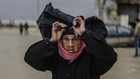 A refugee woman carries her belongings near the Turkish border gate on February 6.