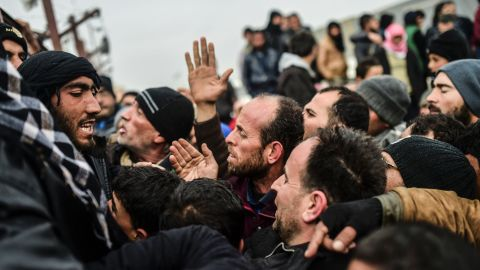 Refugees push each other as they wait for tents near the Turkish border on February 6.