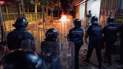 Rioters set fires in Mong Kok as riot police put up shields on February 9 in Hong Kong.