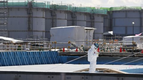 A worker takes notes in front of storage tanks for radioactive water at the Fukushima Daiichi nuclear plant on February 10.