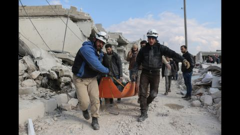 """Members of the """"White Helmets"""" civil defense volunteers carry the body of a man killed in a Russian airstrike in Andan town in the countryside north of of Aleppo."""