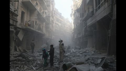 """Two children walk past a """"White Helmet"""" soon after an airstrike hits the Shaar neighborhood of Aleppo."""