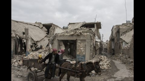 Two men and their donkey navigate the bombed alleyways of Almarja district in eastern Aleppo.
