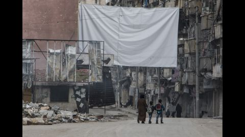 A mother watches over her children as they return from school; the massive sheet hanging in the street is to deter government snipers.