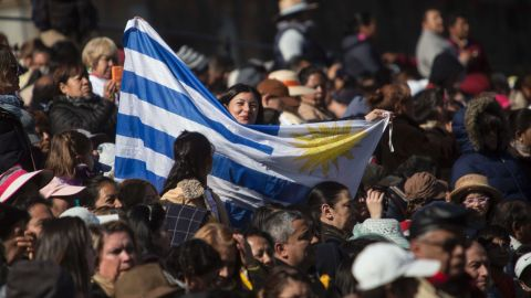 A woman holds an Uruguayan flag while she waits along the route that Pope Francis would take to Mexico City's main square.