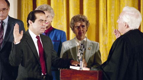 Retiring Chief Justice Warren Burger, right, administers the oath to Scalia, as Scalia's wife, Maureen, holds the Bible on September 26, 1986. Scalia was the 103rd person to sit on the court.