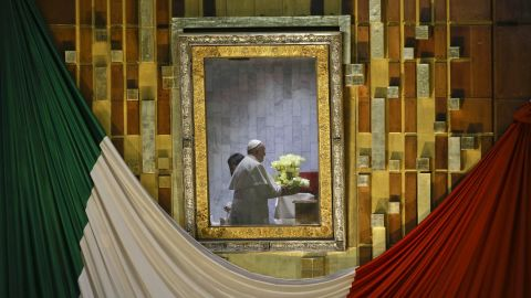Pope Francis, reflected in the frame that holds the image of the Virgin of Guadalupe, holds a bouquet of flowers as he prays to her inside the basilica built in her honor.