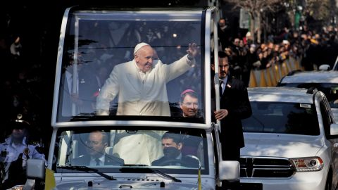 """Pope Francis waves from his """"Popemobile"""" on his way to take a helicopter to Ecatepec."""