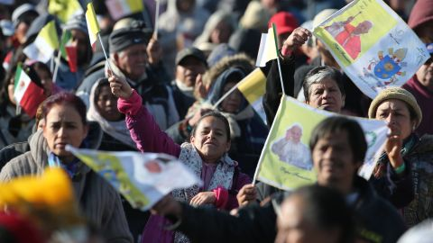 Pilgrims wave flags as they wait for Pope Francis to arrive in Ecatepec on February 14.