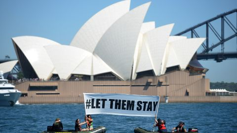 """Members of the environmental group Greenpeace hold up a sign that reads """"#LET THEM STAY"""" in front of the Opera House in Sydney on February 14, 2016.  An Australian hospital in Brisbane has refused to send an asylum-seeker baby back to detention in Nauru as momentum builds across the country against offshore Pacific camps for used by the Australia government for processing refugees who try to get to Australia. AFP PHOTO / Peter PARKS / AFP / PETER PARKS        (Photo credit should read PETER PARKS/AFP/Getty Images)"""