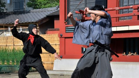 Members of a pantomime group clad in a samurai, left, and ninja costumes perform in Tokyo.
