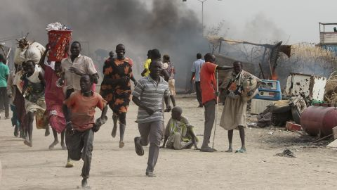 TOPSHOT - South Sudanese civilians flee fighting in an United Nations base in the northeastern town of Malakal on February 18, 2016, where gunmen opened fire on civilians sheltering inside killing at least five people.Gunfire broke out in the base in Malakal in the northeast Upper Nile region on February 17, 2016 night, with clashes continuing on Thursday morning that left large plumes of smoke rising from burning tents in the camp which houses over 47,000 civilians. / AFP / Justin LYNCH        (Photo credit should read JUSTIN LYNCH/AFP/Getty Images)