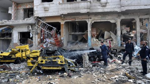 Syrian firefighters spray water on burning car on Sunday, February 21 at the site of a double car bomb attack in the al-Zahraa neighborhood of the Syrian city of Homs.