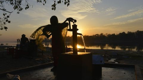 """A girl fills a can with water from a hand pump in a slum area of Lahore, Pakistan. """"More than 1 billion people without energy spend a significant portion of their time collecting wood and water for the basics of life,"""" according to the Gateses."""