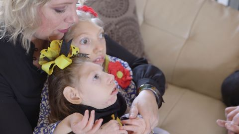 Gwen Hartley cuddles her daughters, Claire and Lola.