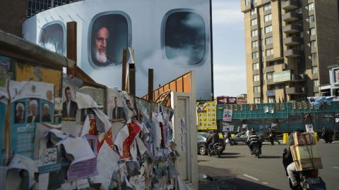 Lurking behind campaign posters is the country's first Supreme Leader, Ruhollah Khomeini, in a billboard commemorating his airborne return to Iran in 1979 after 14 years in exile.