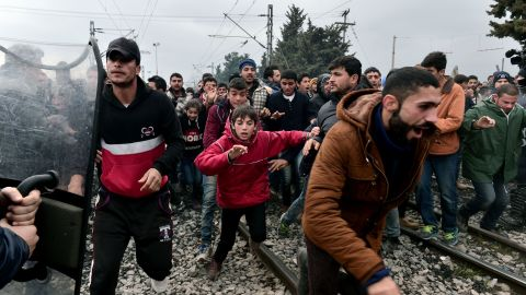 """Migrants run after breaking Greek police blockade towards the border fence of Macedonia near the Greek village of Idomeni, on February 29 , 2016. Macedonian police fired tear gas on February 29, 2016, as a group of some 300 Iraqi and Syrians forced their way through a Greek police cordon and raced towards a railway track between the two countries. With Austria and Balkan states capping the numbers of migrants entering their soil, there has been a swift buildup along the Greece-Macedonia border with Athens warning that the number of people """"trapped"""" could reach up to 70,000 by next month."""