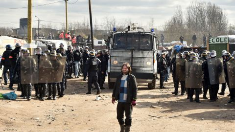 """Police forces stand at the ready during the dismantling of half of the """"Jungle"""" migrant camp in the French northern port city of Calais."""