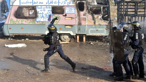 """A police officer throws a tear gas canister during the dismantling of half of the """"Jungle"""" migrant camp."""
