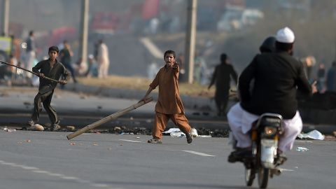 Young Pakistani supporters of Qadri carry sticks as they gesture at a motorcyclist on a blocked main highway during a protest against Qadri's execution in Islamabad on February 29, 2016.