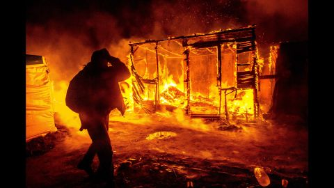 """A migrant walks past a burning shack in the southern part of the """"Jungle"""" migrant camp in Calais, France, in March 2016. Part of the camp was being demolished -- and the inhabitants relocated -- in response to unsanitary conditions at the site."""