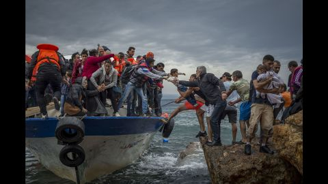 Refugees and migrants get off a fishing boat at the Greek island of Lesbos after crossing the Aegean Sea from Turkey in October 2015.