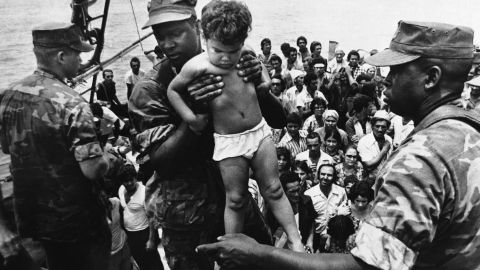 """<strong>Mass exodus from Cuba:</strong> Starting in April 1980, more than <a href=""""http://www.politico.com/story/2009/04/castro-launches-mariel-boatlift-april-20-1980-021421"""" target=""""_blank"""" target=""""_blank"""">125,000 Cubans</a> fled from the port of Mariel to Florida. Associated Press photographer Fernando Yovera captured this image of a U.S. Marine lifting a Cuban child off one of the boats that came into Key West on May 10, 1980. Of the 1,700 boats that made the journey from Cuba that year, many were overcrowded, and 27 migrants died before reaching the United States."""