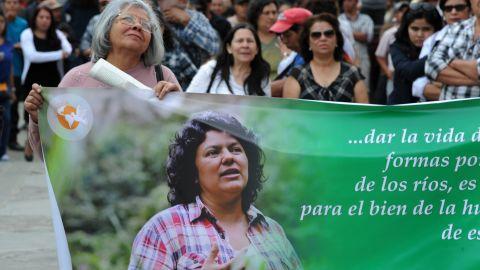 A mourner carries a banner depicting slain activist Berta Cáceres at her funeral.