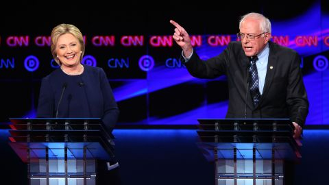 FLINT, MI - MARCH 06:  Democratic presidential candidate Senator Bernie Sanders (D-VT) and Democratic presidential candidate Hillary Clinton speak during the CNN Democratic Presidential Primary Debate at the Whiting Auditorium at the Cultural Center Campus on March 6, 2016 in Flint, Michigan. Voters in Michigan will go to the polls March 8 for the state's primary.  (Photo by Scott Olson/Getty Images)