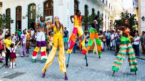 A band and a group of stilt dancers whip around the streets of Old Havana, attracting crowds of visitors. Though Americans are finally normalizing relations with Cuba, tourists from South America, Canada and Europe have been visiting for generations.