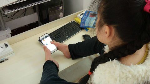 Sun Lukang types on her smartphone with two toes.