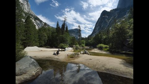 People picnic on the exposed sandy bottom of Mirror Lake that is normally underwater and used by visitors to photograph reflections of the Half Dome rock monolith at Yosemite National Park in California on June 4, 2015.  At first glance the spectacular beauty of the park with its soaring cliffs and picture-postcard valley floor remains unblemished, still enchanting the millions of tourists who flock the landmark every year.But on closer inspection, the drought's effects are clearly visible.      AFP PHOTO/MARK RALSTON        (Photo credit should read MARK RALSTON/AFP/Getty Images)