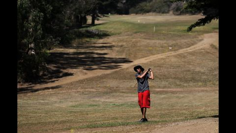 A golfer in San Francisco hits a shot in July. After Gov. Jerry Brown ordered a statewide water-use reduction of 25%, golf courses have been struggling to keep their fairways and greens watered.
