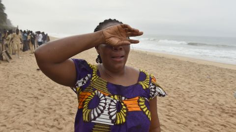 A woman cries at the beach as she looks for her son on March 14.