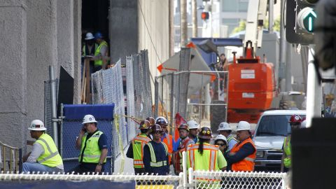 Construction workers gather at the base of the Wilshire Grand Tower on South Figueroa Street where a worker fell to his death on Thursday, March 17, 2016. A fire department spokesperson said the the construction worker plunged 50 stories to his death from the building under construction and hit the back of a passing car in downtown Los Angeles. (AP Photo/Nick Ut)