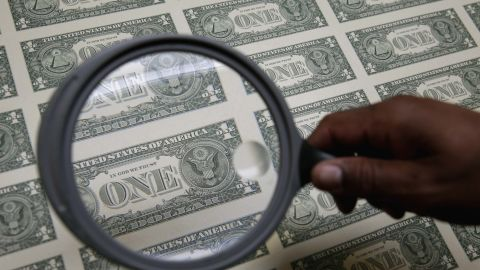 United States one dollar bills are inspected under a magnifying glass during production at the Bureau of Engraving and Printing in Washington.