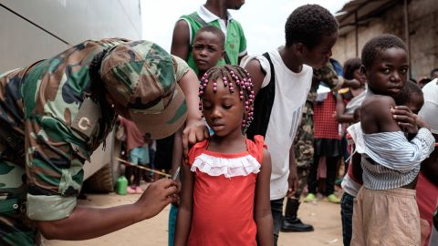 Angolan military administers a yellow fever vaccine to a child at 'Quilometro 30' market, Luanda, Angola on February 16, 2016. This market in the Angolan capital was considered the center of the yellow fever outbreak killing 51 people out of 240 cases since December of 2015.