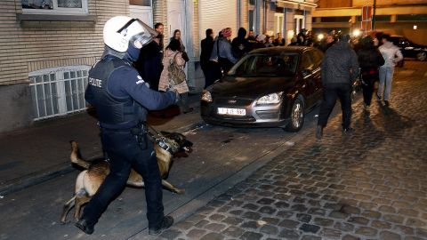 A policeman and a police dog face a crowd  during a police operation in the Molenbeek-Saint-Jean district in Brussels, on March 18, 2016, as part of the investigation into the Paris November attacks.The main suspect in the jihadist attacks on Paris in November, Salah Abdeslam, was arrested in a raid in Brussels on March 18, French police sources said. / AFP PHOTO / BELGA / DIRK WAEM / Belgium OUTDIRK WAEM/AFP/Getty Images