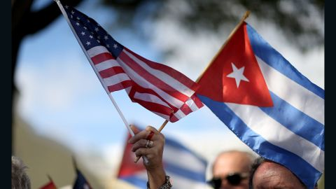MIAMI, FL - DECEMBER 20: A protester holds an American flag and a Cuban one as she joins with others opposed to U.S. President Barack Obama's announcement earlier in the week of  a change to the United States Cuba policy stand together at Jose Marti park on December 20, 2014 in Miami, Florida. President Obama announced a move toward normalizing the relationship with Cuba after a swap of prisoners took place.  (Photo by Joe Raedle/Getty Images)