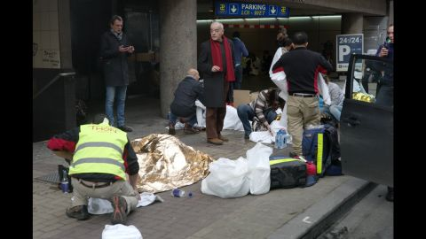Wounded people are treated outside the subway station.