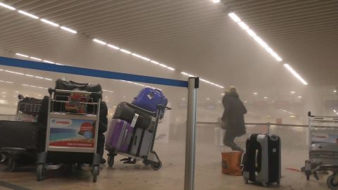 An unidentified traveler runs through the smoke filled terminal at Brussels Airport after explosion rocked the terminal Tuesday morning.