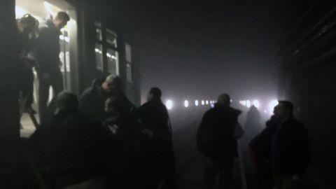 Subway passengers walk along the tracks following a blast at the Maelbeek metro station.